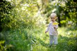 Baby in der Natur mit Blatt in der Hand