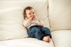 Baby sitzt auf dem Sofa