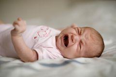 Baby liegt im Bettchen und schreit