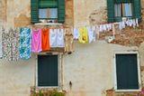 Wäscheleine mit Kleidung vor Hauswand