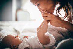 Mutter küsst die Füße ihres Babys