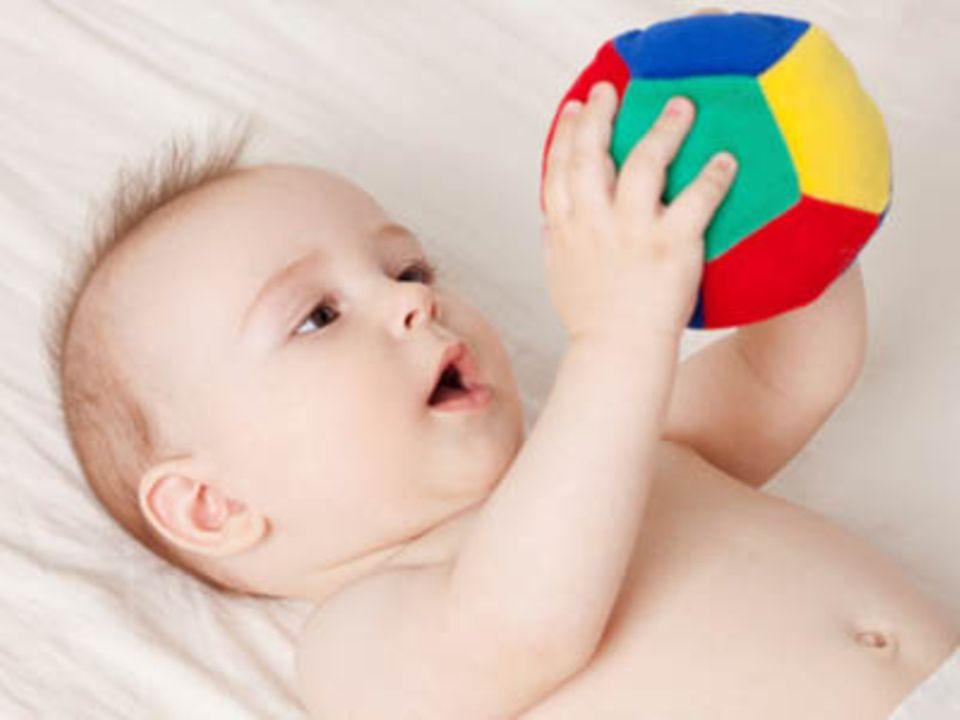 Mit 9 Monaten verfolgen Babys nicht nur Gegenstände mit den Augen, sondern greifen auch nach ihnen.