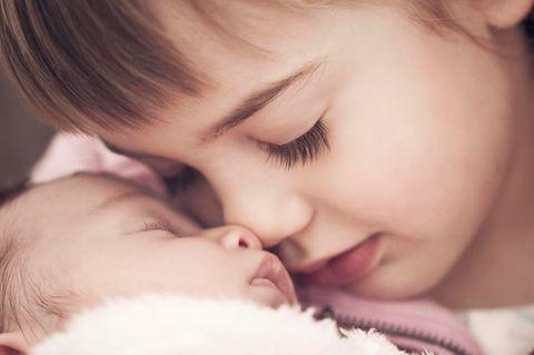 Baby im Arm von Kleinkind