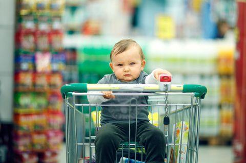 kleiner Junge sitzt im Einkaufswagen und schaut leicht genervt in die Kamera