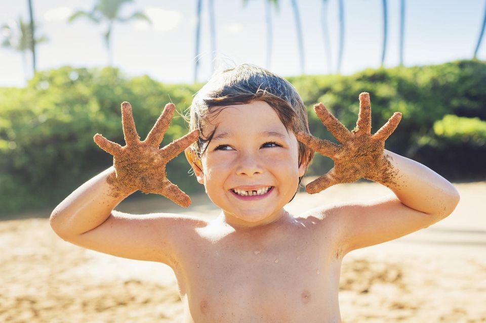 Kind spielt im Sand