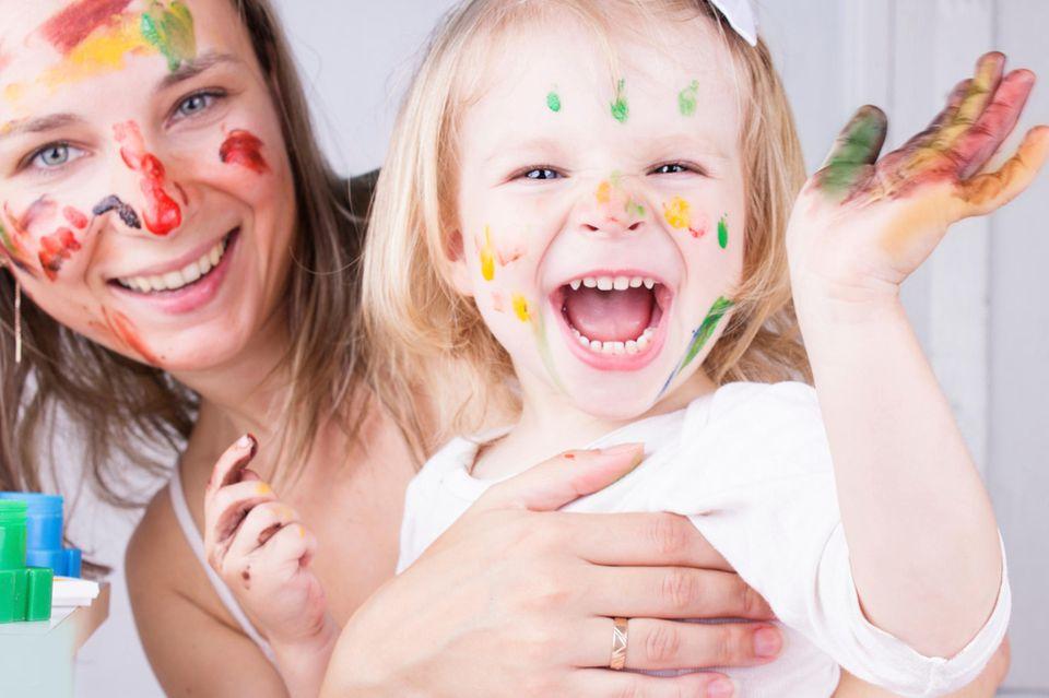 Mutter und Kind malen mit Farben