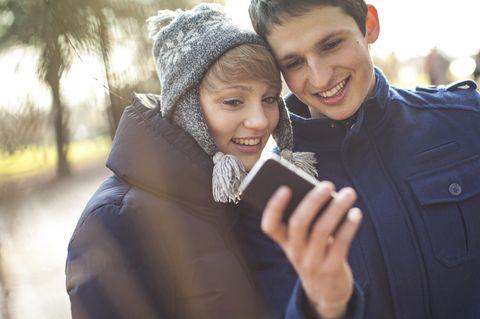 Jugendliche schauen auf ein Handy