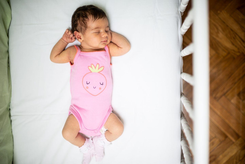 Baby liegt ohne Decke im Babybettchen