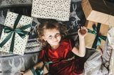 Kind liegt zwischen Geschenken