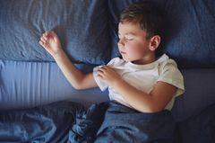 Ein Junge schlaeft in seinem Bett