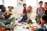 Kinder spielen mit Erwachsenen in einem Spielzimmer