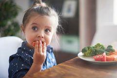 Ein Maedchen isst Gemuese