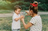 Ein Junge bekommt von seiner Mutter draußen Wasser eingeschenkt