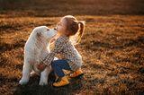 Ein Maedchen spielt draußen mit ihrem weißen Hund