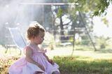 Kleines Mädchen sitzt alleine auf Spielplatz