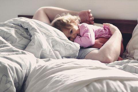 Kleinkind liegt mit Vater im Bett
