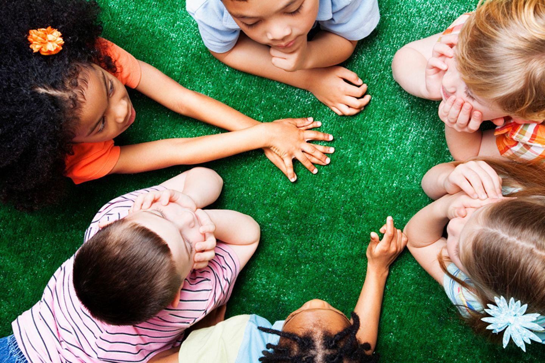Kinder sitzen im Kreis