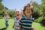 Kinder toben im Garten