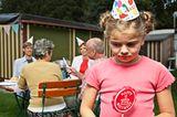 Kind ist traurig, keiner kommt zum Geburtstag, außer Eltern und Großeltern (im Hintergrund)