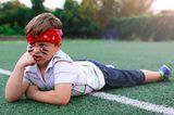 Junge liegt nach Wettkampf/Spielen auf dem Boden, ist sauer/unzufrieden