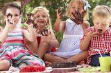 Kinder sitzen am Boden, haben sich die Hände mit Kuchen verschmiert, strecken diese in die Kamera