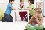 Kind sitzt am Boden, möchte nicht mit den anderen Kindern spielen
