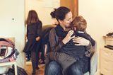 Kind krabbelt auf Mamas Schoß