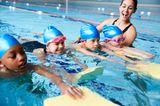 Kinder lernen schwimmen im Hallenbad