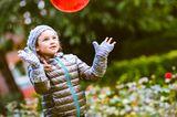 Mädchen spielt mit einem roten Ball