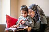 Mädchen und Mama lesen ein Bilderbuch