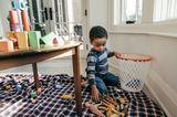 kleiner Junge räumt Spielsachen in einen Korb