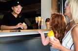 Mädchen kauft mit Mama Eis