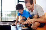 Ein Junge macht mit seinem Vater ein Puzzle