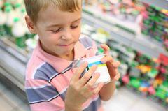 Junge schaut Joghurt Verpackung genauer an, hält diese in seinen Händen