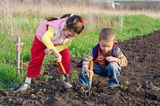 Junge und Mädchen bei der Gartenarbeit/ Feldarbeit im Acker