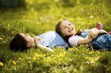 Junge und Mädchen liegen im Gras, lachen