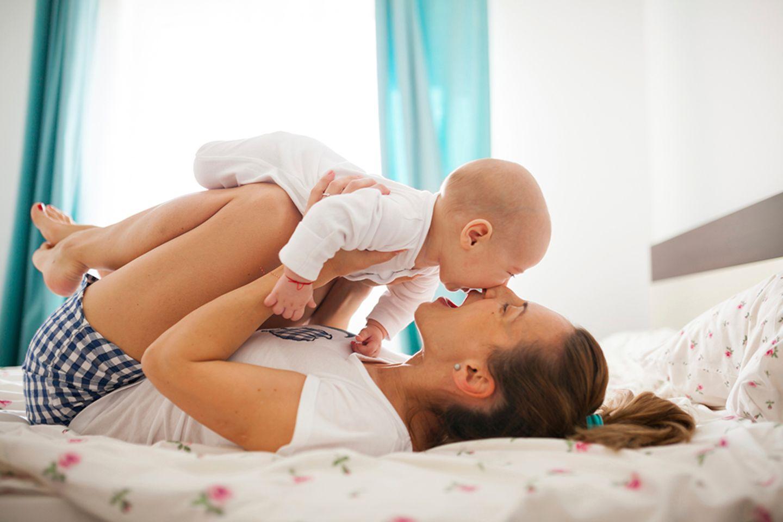 Mutter liegt auf dem Bett, hält Baby über sich, küsst es