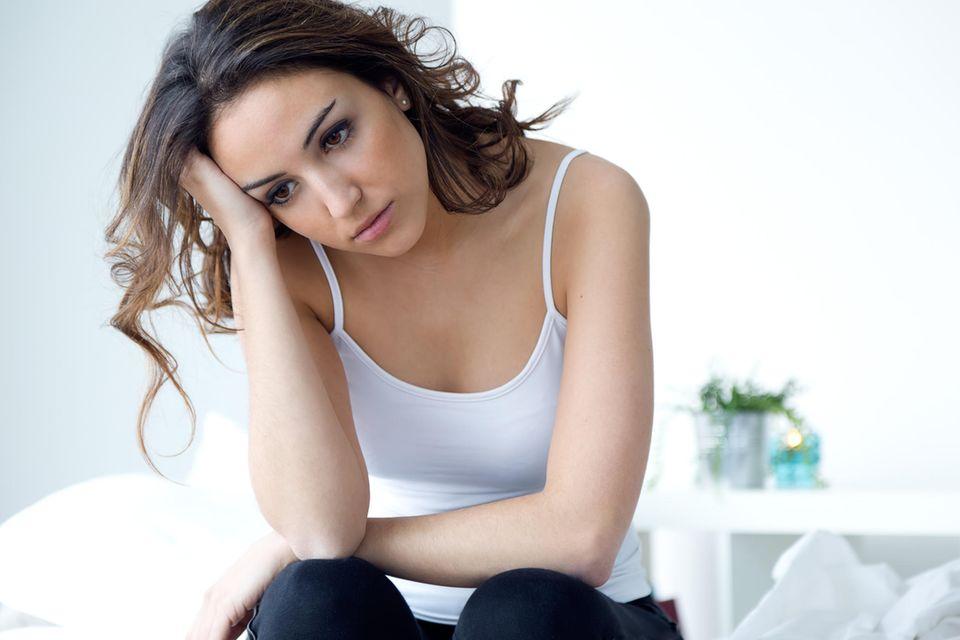 Frau sitzt traurig auf dem Bett