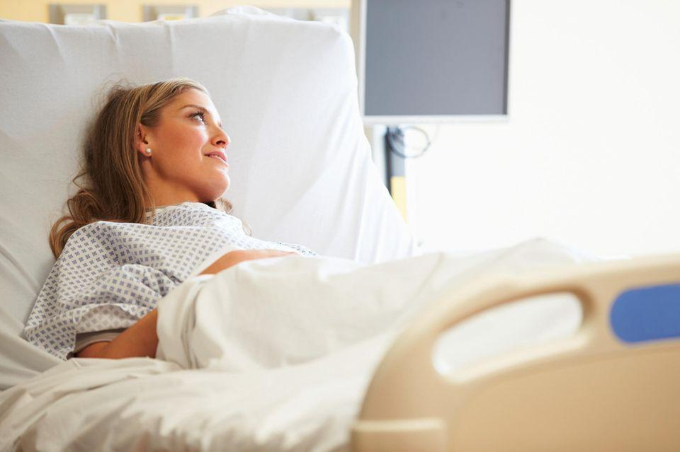 Patientin liegt im Bett, schaut zur Seite, lächelt