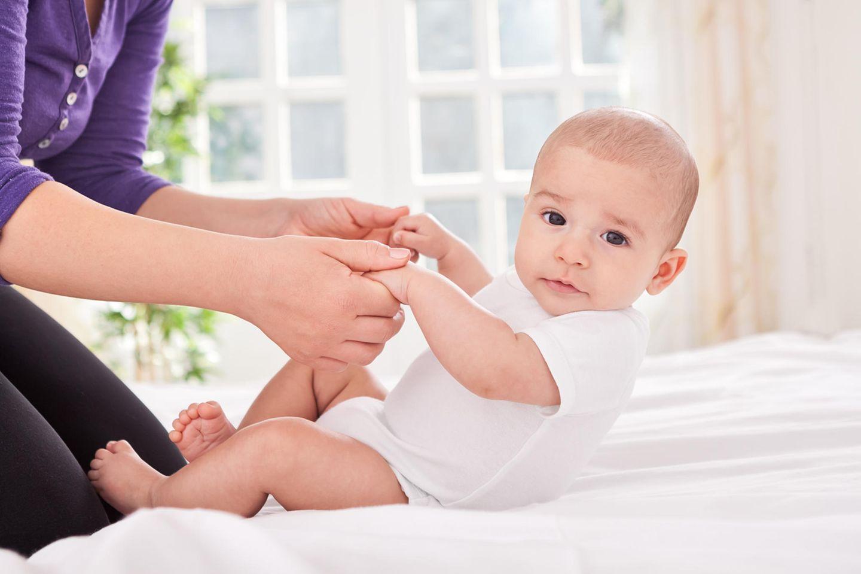 Baby wird an beiden Händen in den Sitz hochgezogen
