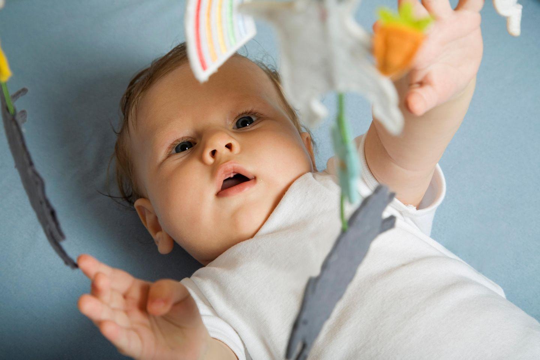 Baby liegt auf dem Rücken, greift mit linken Arm nach Mobile