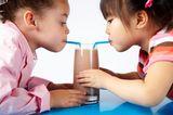 Mädchen trinken aus einen Glas mit 2 Strohhalmen Kakao