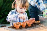 Mädchen pflanzt Samen in kleine Töpfchen