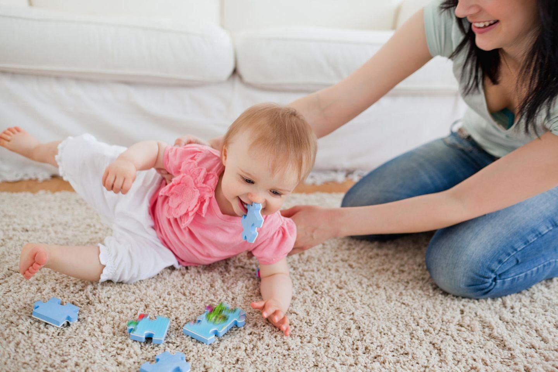 Baby sitzt auf Teppich, kippt zur Seite, Mutter fängt es auf