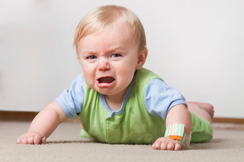 Baby liegt auf dem Bauch, stützt Arme auf, ist zornig, weint