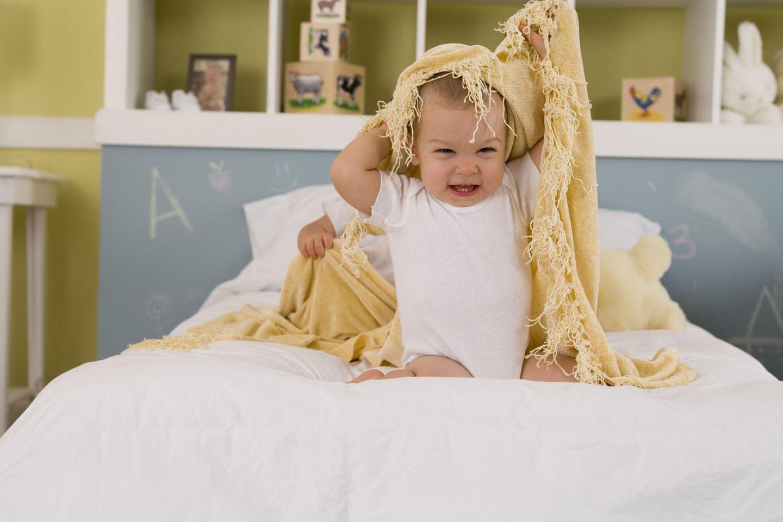 Baby sitz auf dem Bett, möchte sich unter einen Decke verstecken, lacht in die Kamera