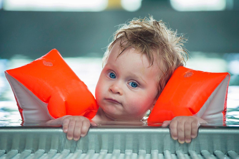 Baby mit Schwimmflügeln, hält sich am Beckenrand fest
