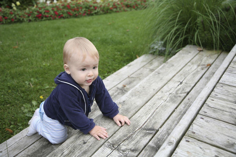 Baby klettert 3 Holzstufen( im Garten) hoch