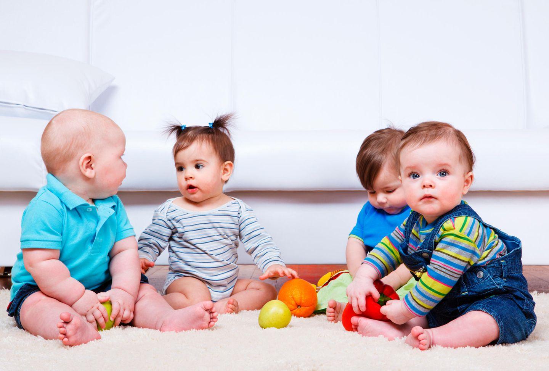 Babys sitzen auf dem Boden, spielen