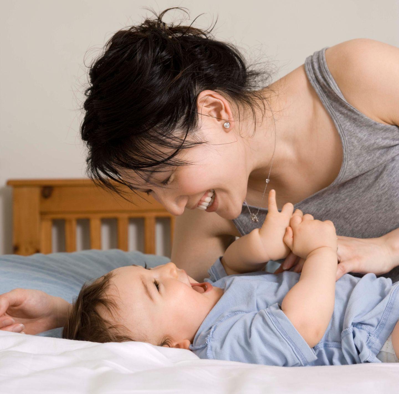 Mutter und Baby liegen im Bett, lachen